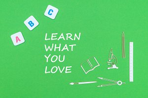 text learn what you love, from above wooden minitures school supplies and abc letters on green background