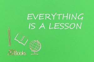 text everyting is a lesson, school supplies wooden miniatures on green background