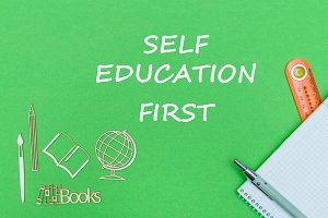 text self education first, school supplies wooden miniatures, notebook on green background