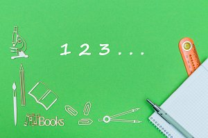 numbers 1,2,3, school supplies wooden miniatures, notebook with ruler, pen on green backboard