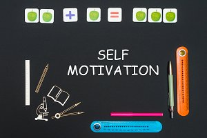 Above stationery supplies and text self motivation on blackboard