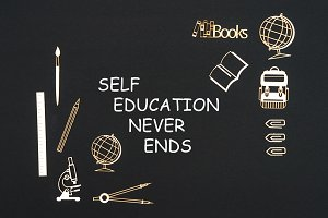 School supplies placed on black background with text self education never ends