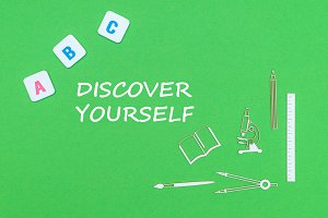text discover yourself, from above wooden minitures school supplies and abc letters on green background