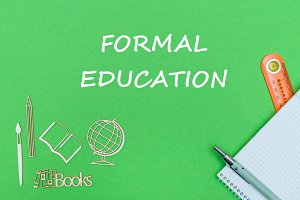 text formal education, school supplies wooden miniatures, notebook on green background