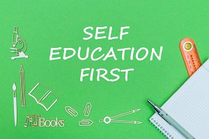 text self education first, school supplies wooden miniatures, notebook with ruler, pen on green backboard