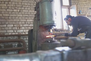 Molten metal is processed under pressure in the hands of a blacksmith, wide angle