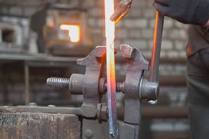 Close up view - hands of Blacksmith with gloves in forge makes steel knife