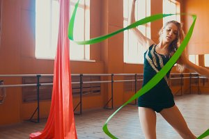 Young attractive woman trains with a green ribbon - gymnastics exercise in studio with mirror