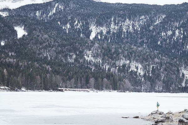 Tourist at winter mountain lake