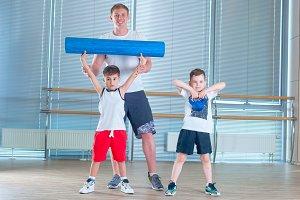 Group of children doing kids gymnastics in gym with teacher. Happy sporty children in gym. foam roller