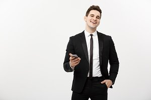 Business Concept: Happy young businessmanman in smart suit typing sms on gray background