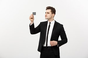 Portrait of a businessman holding a credit card and seriously checking isolated over grey background.