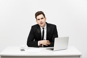 caucasian businessman sitting at desk looking and thinking in office.
