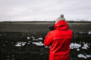 Photographer at black sand beach. Rear view