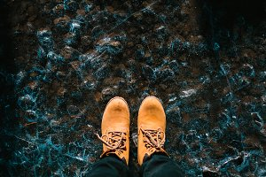 A pair of brown hiking boot on ice textured background. Iceland. Copy space