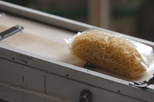 Food factory - conveyor with plastic pack of macaroni