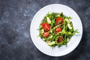 Healthy vegan salad from arugula, avocado and tomatoes.