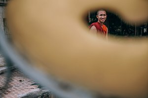 Happy Young Monk Behind Temple Gate