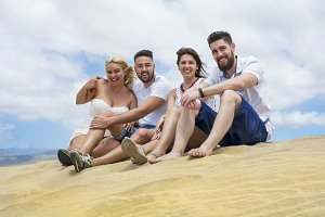 Friends sitting on the sand dunes.