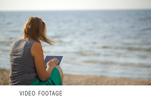 Woman sitting on beach by the sea