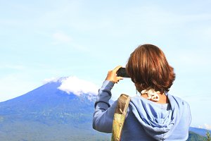 Woman taking photo of the mountains with smartphone
