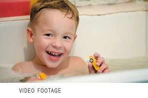 Happy little boy in bath with toys
