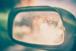 Vintage Style - blurred luxury car on road with side mirror