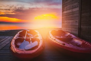 The beautiful sunset with couple red Kayak boat with sun lay.