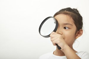 asian child girl with a magnifying glass at the doctor ophthalmologist