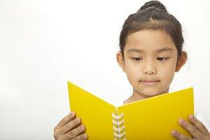 Beautiful cute little  asian school girl who reads a book