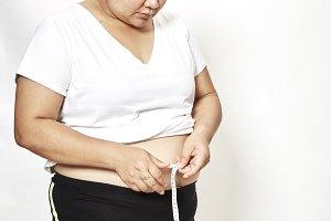 Woman measuring her waistline fat tummy