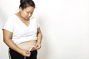 Woman measuring her waistline fat tummy