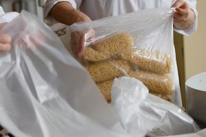 Worker packaging macaroni from the conveyor belt in a pasta factory