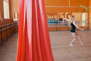 Red silk in front of young woman training a gymnastics exercise with a ribbon - de-focused