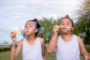 girl's enjoys blowing soap bubble