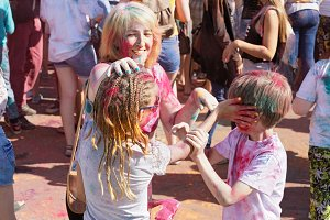 Cheerful mother and her children smear dry paint on each other's body and clothes