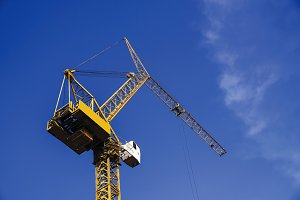 Crane in construction site with blue