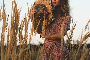 Beautiful woman in field at summer sunset