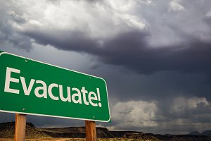 Evacuate Green Road Sign with Clouds