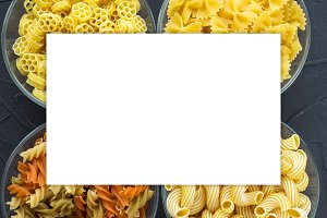 Macaroni ruote Different pasta in a glass bowl with spiral pasta on a textured black background, close-up view from the top. White space for text and ideas.