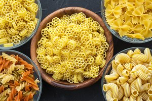Macaroni ruote A wooden white and glass bowl with a variety of spiral pasta on a textured black background, close-up view from the top.