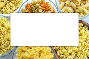 Macaroni ruote Different pasta in a glass and wooden bowl with pasta spirals on a white background, close-up view from the top. White space for text and ideas.