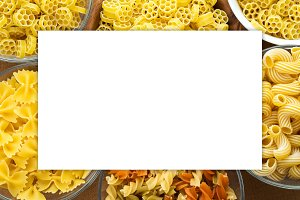 Macaroni ruote Different pasta in a glass and wooden bowl with pasta spirals on a brown rustic background, close-up view from the top. White space for text and ideas.