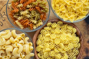 Macaroni ruote Different pasta in a glass and wooden bowl with pasta spirals on a decorated rustic wooden background, close-up view from the top.