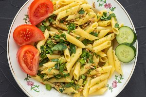 Plate with pasta, seasoned with dill parsley and greens, sliced cucumbers. View from the top, a black background.