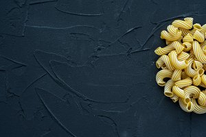 Macaroni rigati background with pasta on a black background with a side. A view from the top, a close-up of a texture. Free space for text.