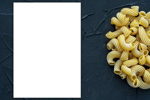 Macaroni rigati background with pasta on a black background with a side. A view from the top, a close-up of a texture. White space for text and ideas.