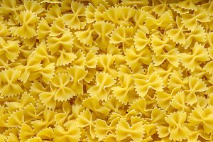 farfalle macaroni background with pasta. A view from the top, a close-up of a texture.