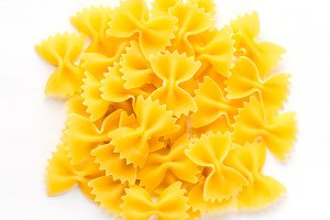 farfalle macaroni background with pasta on white isolated background with shadow. A view from the top, a close-up of a texture.