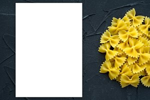 farfalle macaroni background with pasta on a black background with a side. A view from the top, a close-up of a texture. White space for text and ideas.